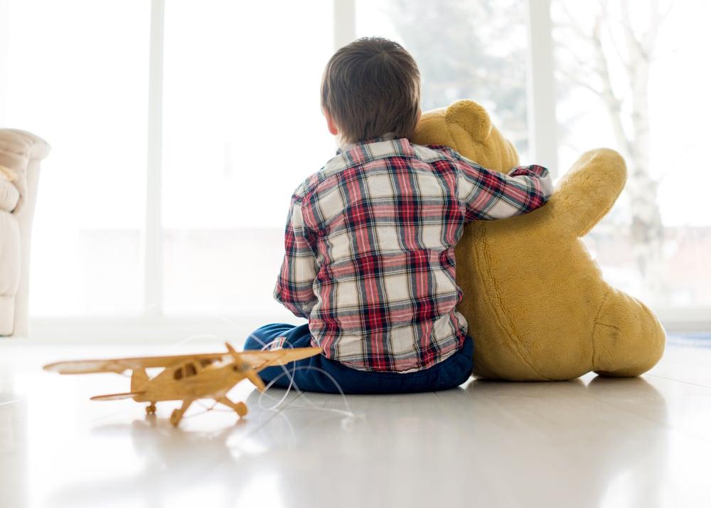 Portræt af barn sidder i stuen med bamse