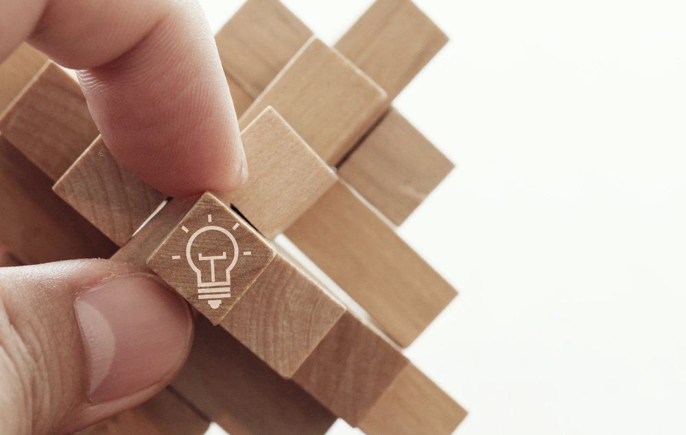 close up of hand showing illuminated light bulb icon on a wooden block puzzle as innovation concept