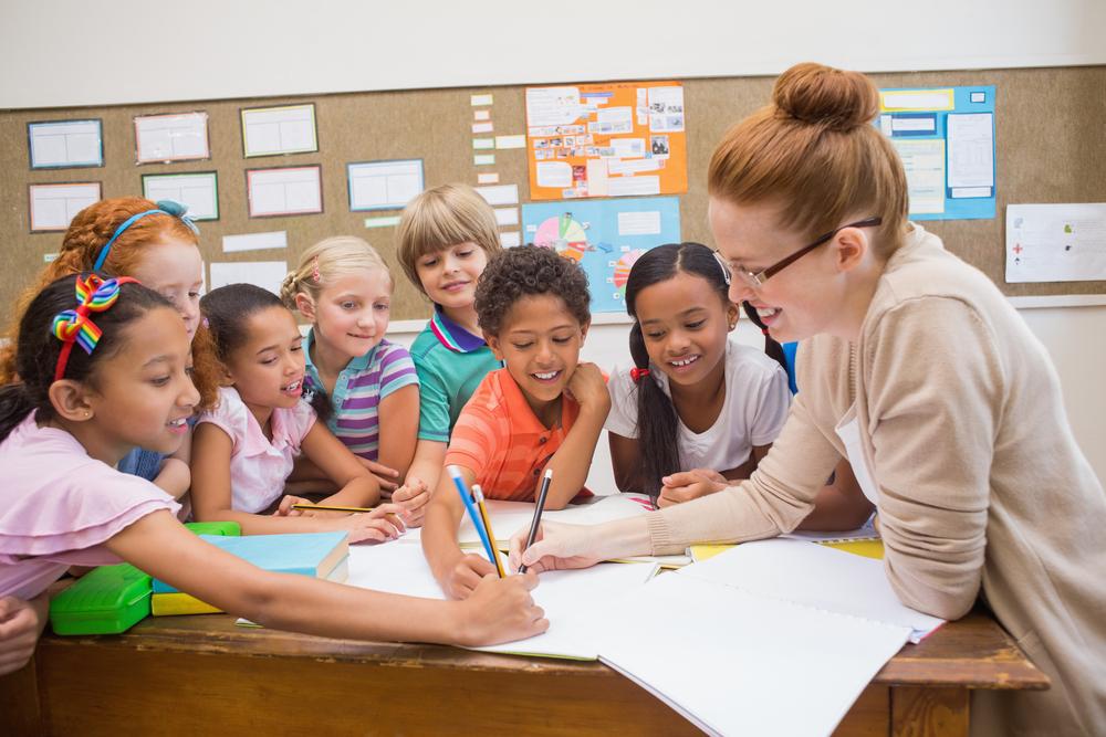 Lærer og elever, der arbejder ved skrivebordet sammen på folkeskolen