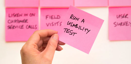 Post-its on a wall and a hand holding one post it saying run a usability test