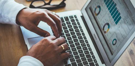 Solteq blog - miehen kädet näppäimistöllä, kannettavan tietokoneen ruudulla graafeja