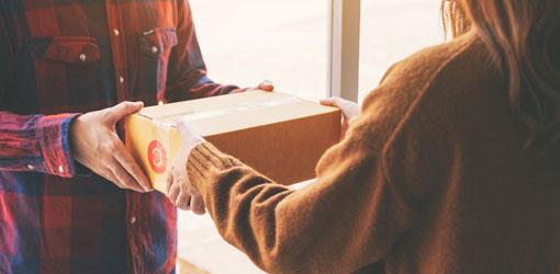 Solteq blog - ruutupaitainen kuriiri toimittaa verkkokauppatilausta beigessä paidassa vastaanottavalle asiakkaalle