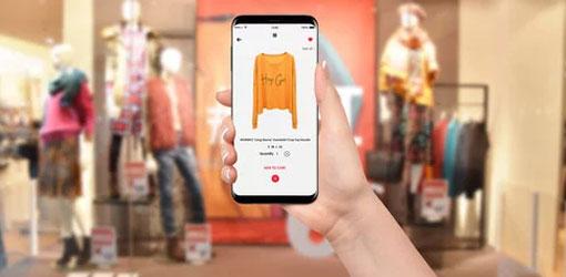 Naisen käsi pitää matkapuhelinta missä näkyy verkkokaupan tuote, taustalla vaatekaupan liiketila.