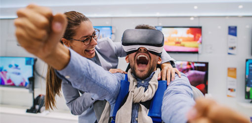 Mies ja nainen nauravat ja kokeilevat virtuaalilaseja kodinkonekaupassa