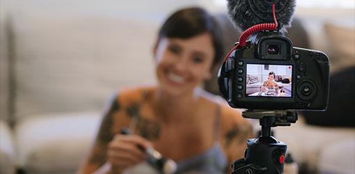 Hymyilevä tummahiuksinen nainen katsoo kameraan kuvatessaan verkkokauppaan tuote-esittelyvideota