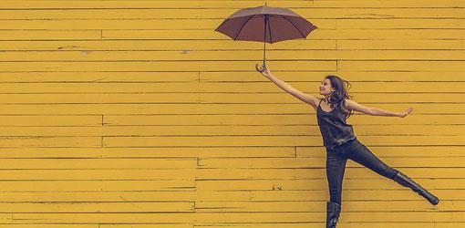 Nainen mustissa vaatteissa pitää sateenvarjoa keltaisen puuseinän edessä