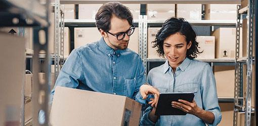 Naine ja mies sinisissä paidoissa tutkivat master data tietoja yrityksen varastossa