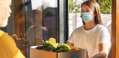 Lähetti maski kasvoilla toimittaa ruuan verkkokauppatilausta