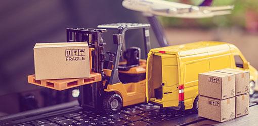 B2B-verkkokaupan paketteja, trukki, lentokone ja keltainen pakettiauto kannettavan tietokoneen näppäimistöllä