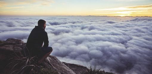 Mand på plads på toppen af bjerget og kigger over skyerne