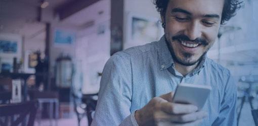 Smilende mørkhåret mand ser på sin mobiltelefon