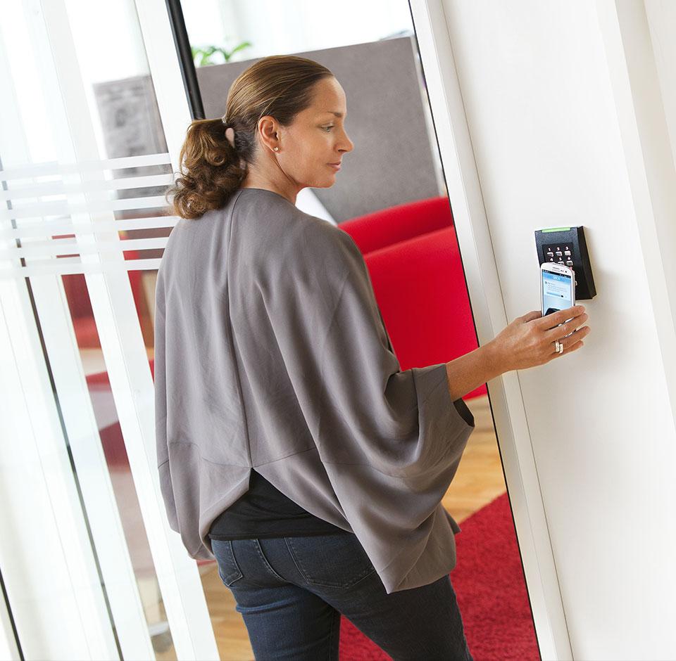 Assa Abloy - en kvinde i en grå tunika åbner den elektriske dør på hoveddøren til en enebolig med en telefon