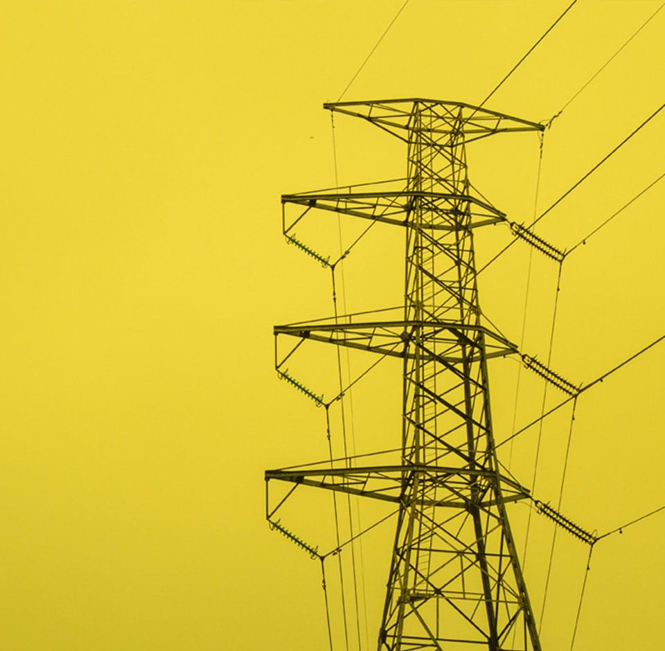 Elenia - korkea sähkötolppa vasten keltaista taustaa
