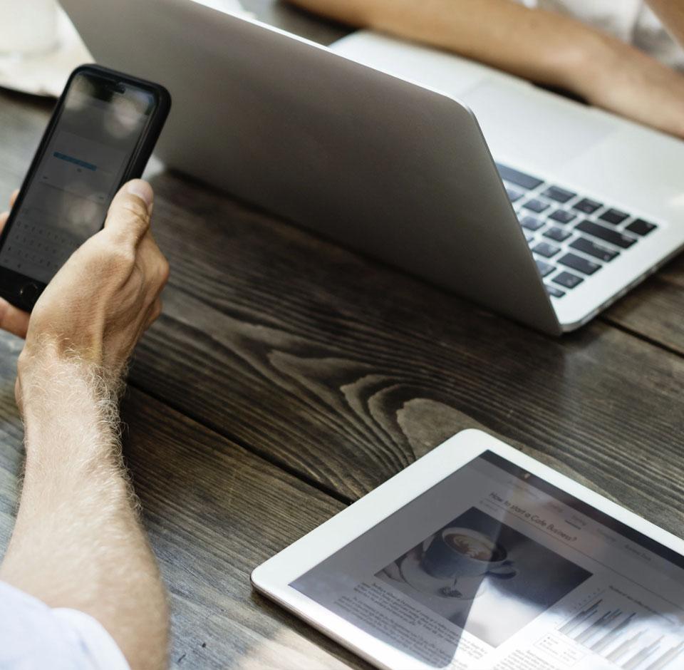 Mann og kvinne som forhandler kaffe med laptop og mobiltelefon