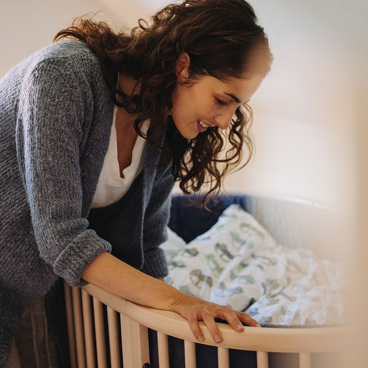 Kvinde sætter en baby i en krybbe