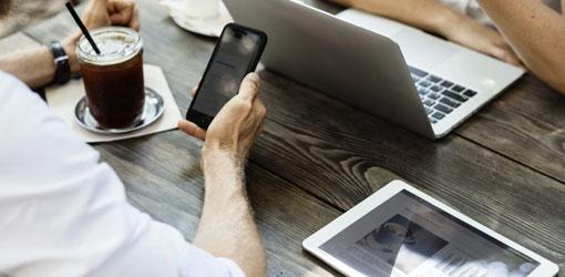 Mand og kvinde forhandler om kaffe med bærbar computer og mobiltelefon mobiltelefon