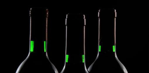 Alko - kolme viinipulloa kuvattuna mustaa taustaa vasten