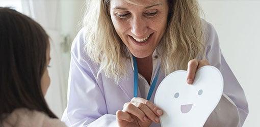 Kvindelig tandlæge, der viser et tandbillede til en barnepatient