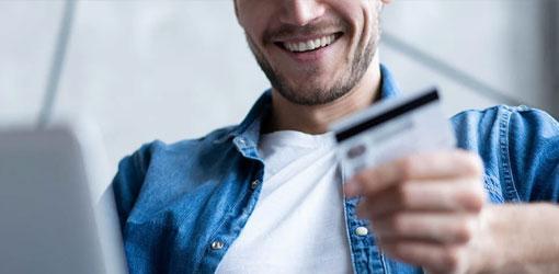 Hymyilevä mies sinisessä farkkupaidassa katsoo maksukortti tehdessään verkkokauppaostoa