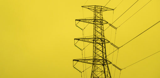 Elenia - suuri sähkötolppa vasten keltaista taustaa