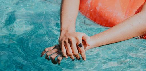 Holiday Club Resorts - Nainen ui uimarenkaalla turkoosissa uima-altaassa kylpylässä