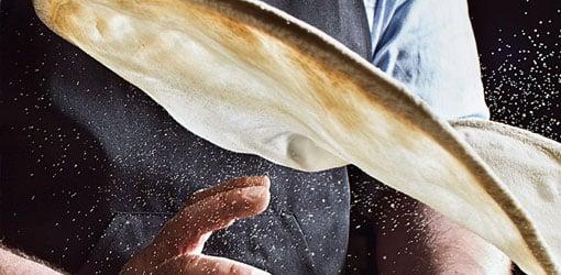 Kotipizza - Pitsan valmistaja pyörittää pitsataikinaa ilmassa