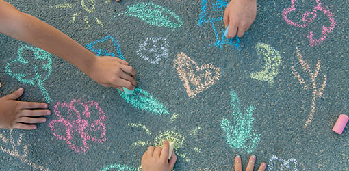 Barn trekker på asfalt med fargestifter