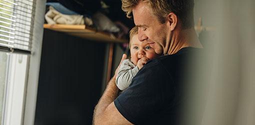 Mand i en sort t-shirt, der holder en baby