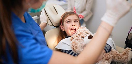 Pige med en bamse på en tandlæge stol