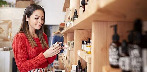 Nuori tummahiuksinen nainen tutkii kosmetiikka tuotteita kaupan hyllyn edessä