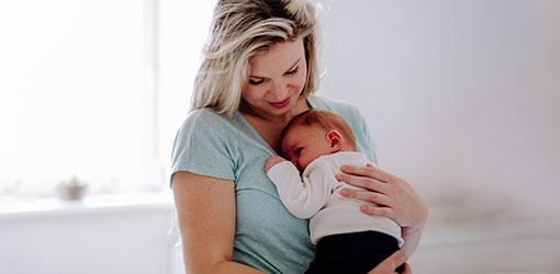 Kvinde i en grøn t-shirt, der holder en baby