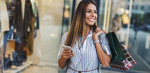 Kvinne som går med mobil og gjør e-handel innkjøp