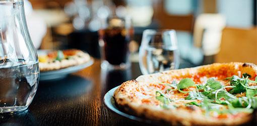 Ravintolan pöydällä pizzoja ja vesikannu