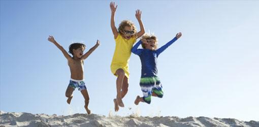 Tre glade børn hopper fra klit på en strand