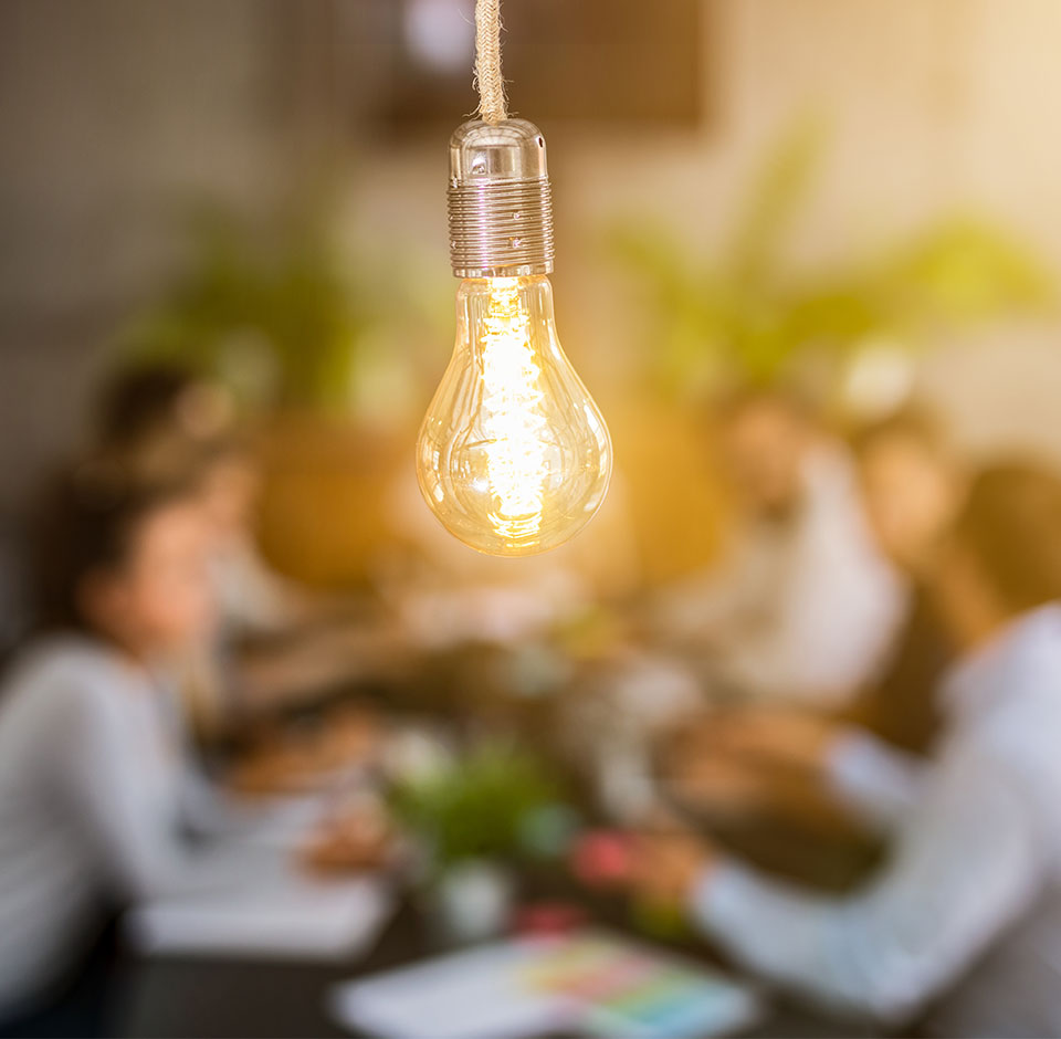 A group of people listening to consulting services at a table, in front of an electric lamp