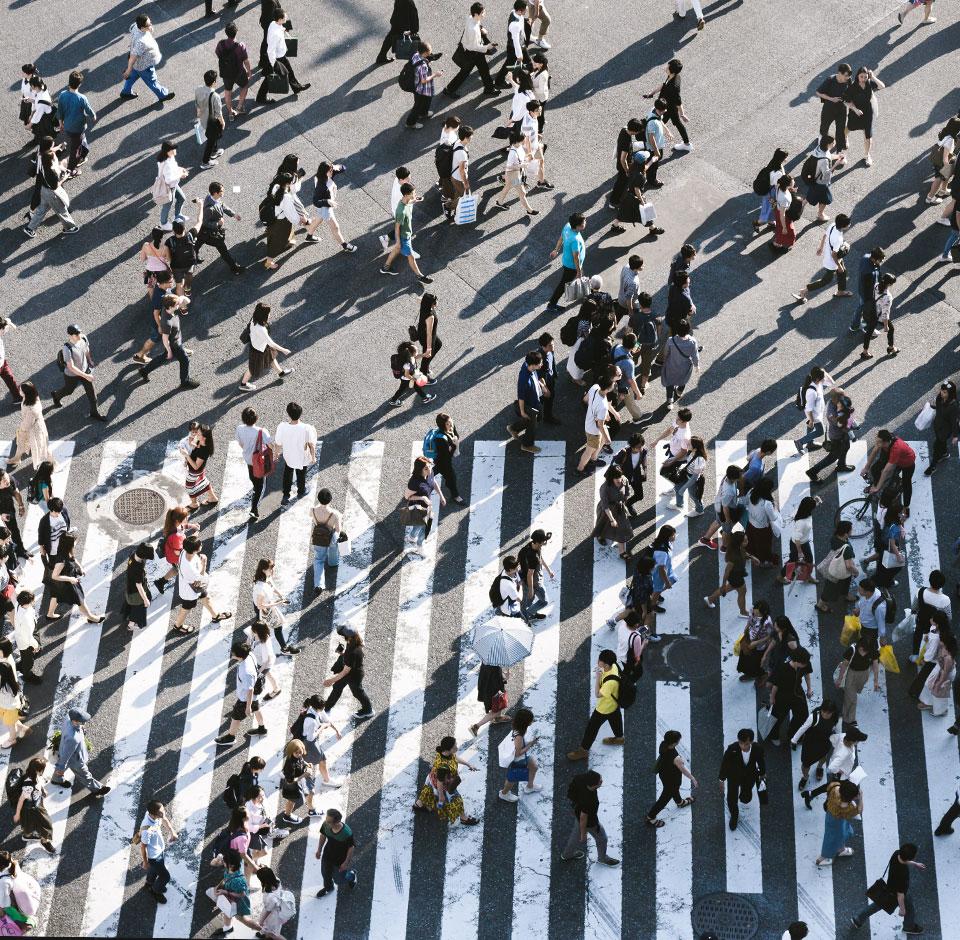 Asiakastietojen tuoreutus - Asiakkaita kävelee kadulla osittain suojatien päällä