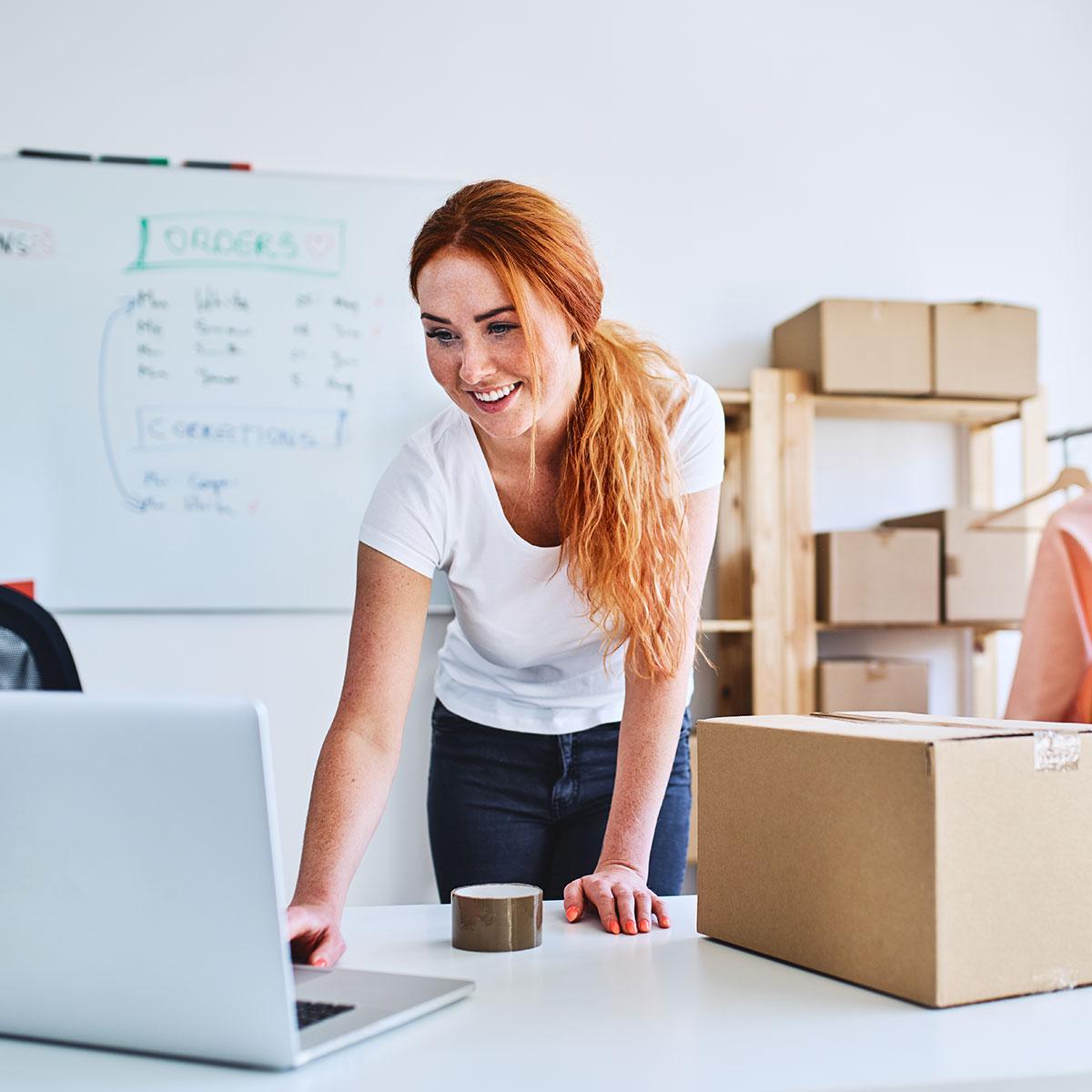 Iloinen punahiuksinen nainen valkoisessa t-paidassa paketoi Magento verkkokaupan tilausta
