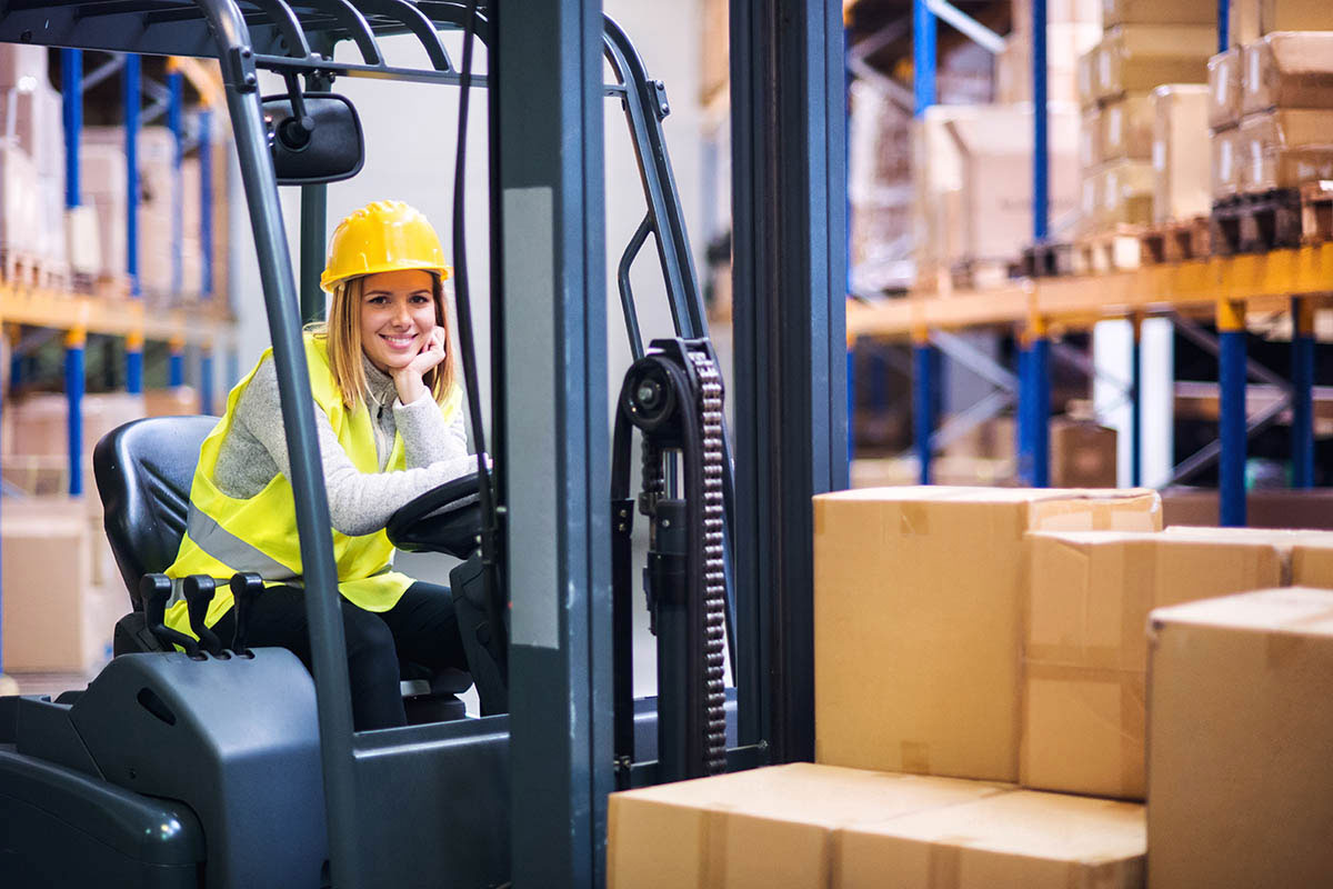 A smiling woman in a yellow vest and helmet leans behind the wheel of a truck in a warehouse