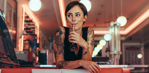Dark haired young woman waitress in restaurant drinking soda
