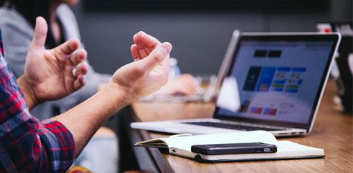 ERP - Mand og kvinde på et møde om ERP-løsning med bærbar computer på bordet