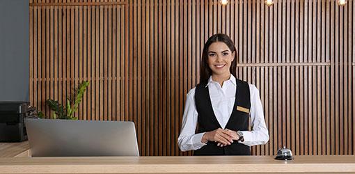 Hotel receptionist, der byder gæsterne velkommen
