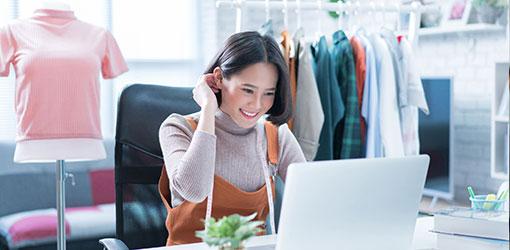Hymyilevä vaatemyymälän verkkokauppias katsoo kannettavan tietokoneen näytöltä WooCommerce verkkokauppansa kassaintegraation tietoja, taustalla vaatekaupan vaatteita rekissä ja vaaleanpunainen neulepaita sovitusnuken päällä
