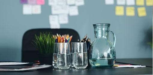 Värikyniä, juomalasit ja vesikannut toimiston pöydällä, taustalla post-it lappuja seinällä