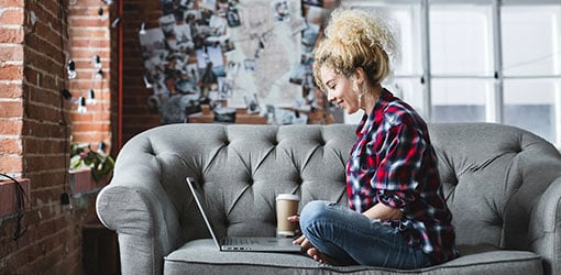 Young woman sitting on a sofa at loft apartment and doing online shopping in ecommerce