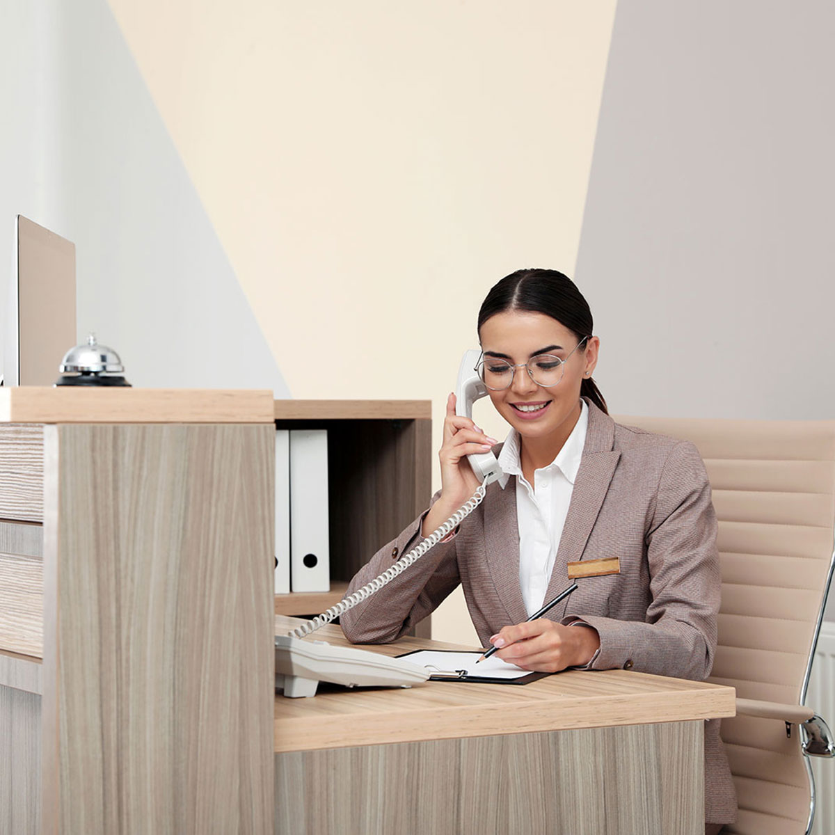 hotellbokningssystem - support - Hotellreceptionisten tar ett samtal framför ett skrivbord